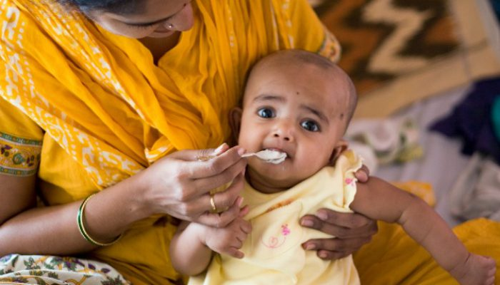 Getting her first spoon-ful of Rice. This is very soft boiled rice, some sugar and ghee. Notice the custom made silver spoon - spiffy eh!